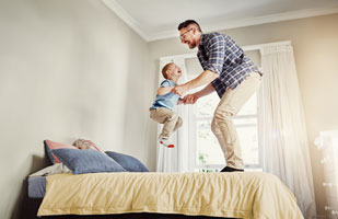 Dad and son jumping on bed